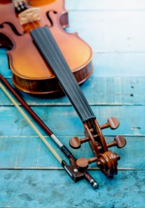 Violin and violin bridge on wood floor with lighting